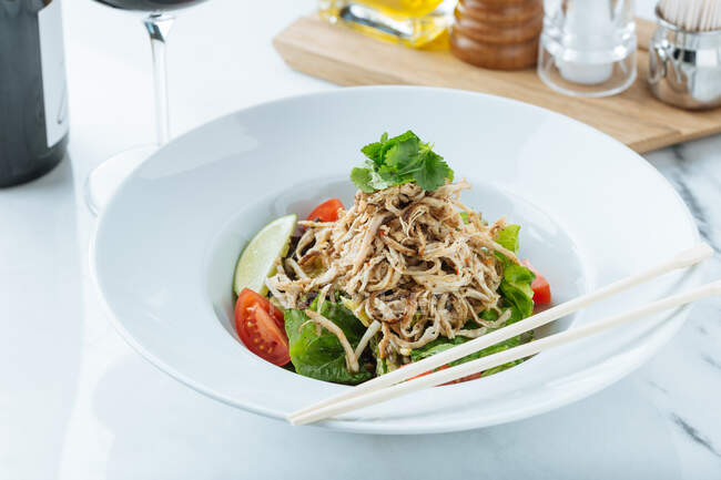 From above of fresh salad of tomatoes lime and lettuce served with cuts of meat and parsley in restaurant — Foto stock