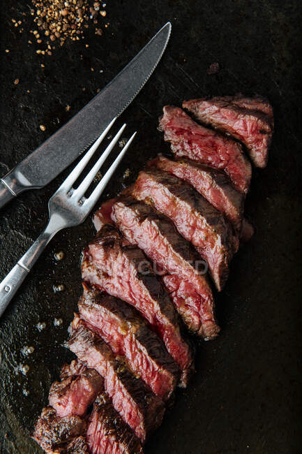 Top view of medium rare slices steak on table with fork and knife in restaurant — Fotografia de Stock