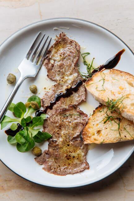 Vista superior de saborosos pedaços fritos de carne em prato branco com pão assado decorado com molho de vegetação e garfo de metal no restaurante — Fotografia de Stock