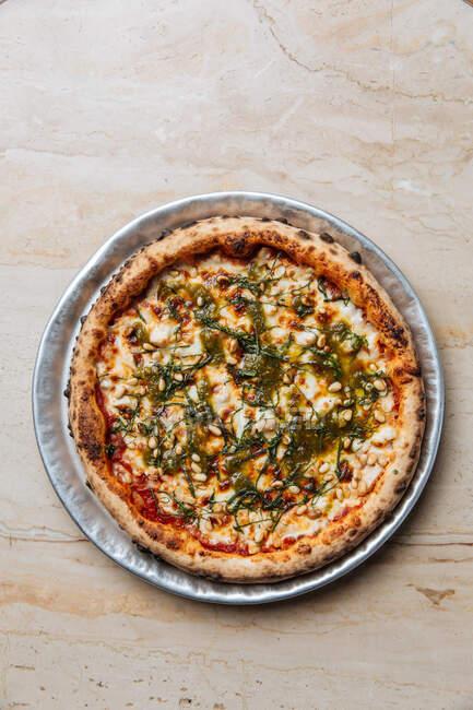 Dall'alto della succosa pizza vegetariana al forno servita con formaggio, semi ed erbe aromatiche sul tavolo del ristorante — Foto stock