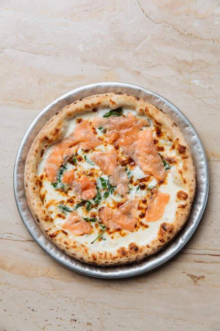 Vista dall'alto della pizza fresca al forno con formaggio e fette di pesce rosso decorate con erbe aromatiche nel ristorante — Foto stock