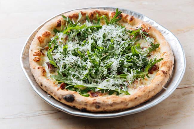 Nahaufnahme von oben von leckerer gebackener Pizza mit grünem Rucola und geriebenem Käse im Restaurant — Stockfoto
