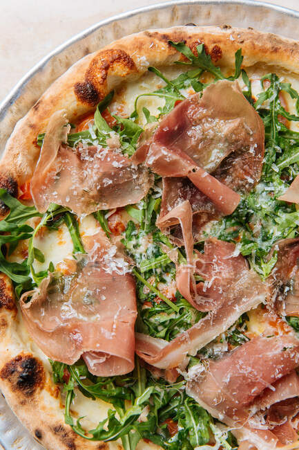 Top view of tasty pizza with thin slices of bacon and fresh greenery on plate in restaurant — Stock Photo