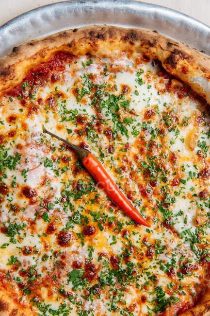 Vista superior de pizza redonda con salsa de tomate y queso derretido adornado con pimiento verde picado y pimienta de cayena sola - foto de stock