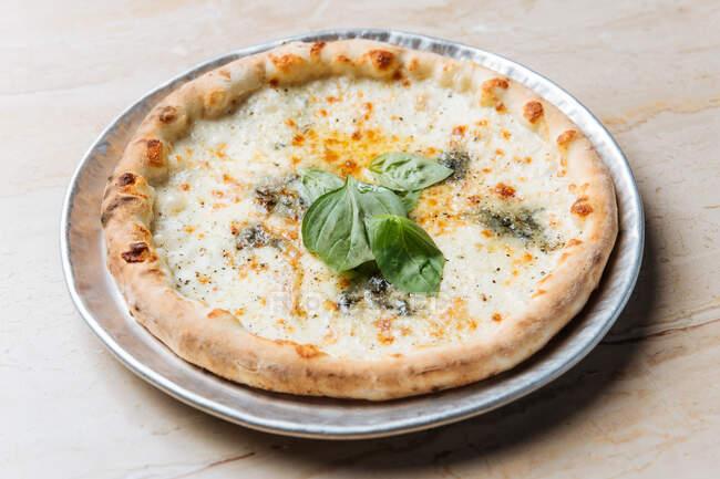 Dall'alto di pizza al forno succosa servita con formaggio ed erbe di basilico sul tavolo nel ristorante — Foto stock