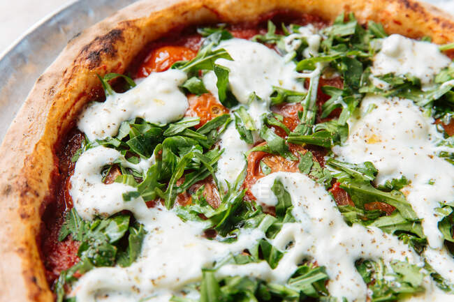 Von oben dünne gebackene Pizza mit dickem Rand gefüllt mit Kirschtomaten und gehacktem Rucola mit weißer Ranch-Sauce — Stockfoto