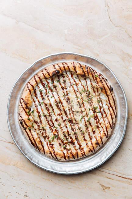 З верху хрусткої піци з товстим краєм, наповненим бананами, зверху потовченими горіхами і нарізаним м