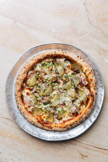 Верхній вид круглої піци з розплавленим сиром моцарелла з нарізаним червонуватим і цибулею з огірками. — стокове фото