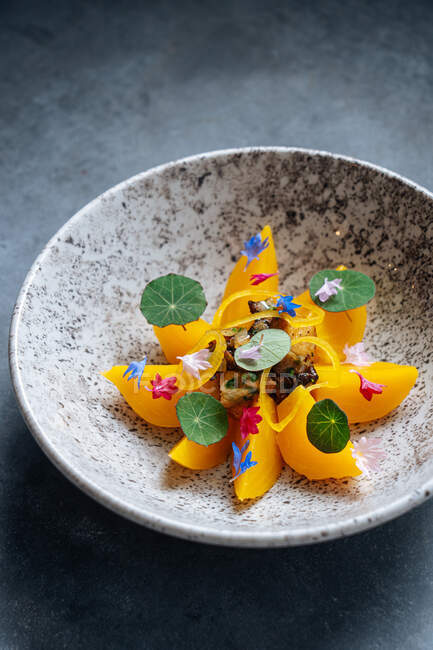 De arriba del trozo de la fruta anaranjada que lleva en el círculo con las setas fritas blancas en el centro en el plato de estilo - foto de stock