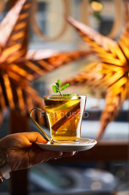 Crop hand with hot cocktail in glass decorated with slice of lemon anise and cinnamon — Stock Photo