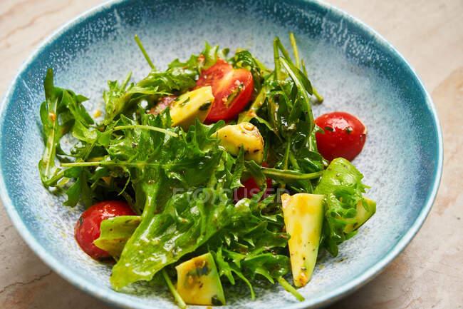 Сверху салат с кусочками вишневого помидора авокадо и листьями аругулы, заправленный оливковым маслом в голубой миске — стоковое фото