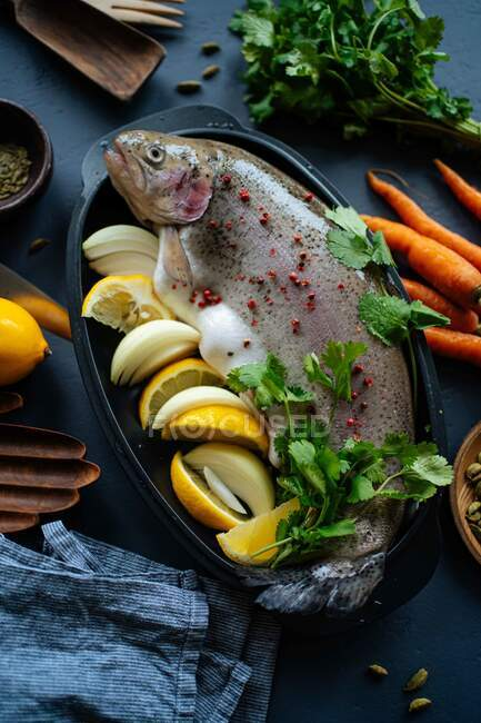 Overhead fresh fish placed in pot with pastry and lemon with onion during dinner preparation in kitchen — Stock Photo