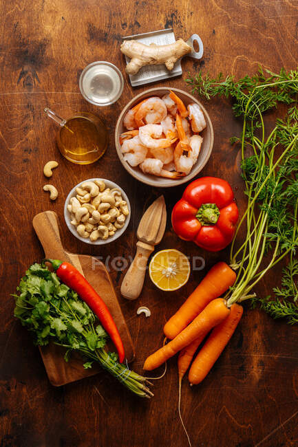 Top view of various ripe vegetables and herbs placed near juicer and boiled shrimps on wooden table in kitchen — Stock Photo