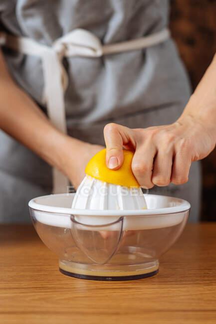 Personne méconnaissable dans le tablier en utilisant presse-agrumes manuel pour presser le jus de citron frais pendant la cuisson dans la cuisine à la maison — Photo de stock