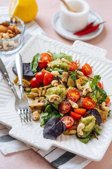 Appetizing colorful healthy fresh salad with vegetables and cashew nuts garnished with basil leaves served on white plate with forks — Stock Photo