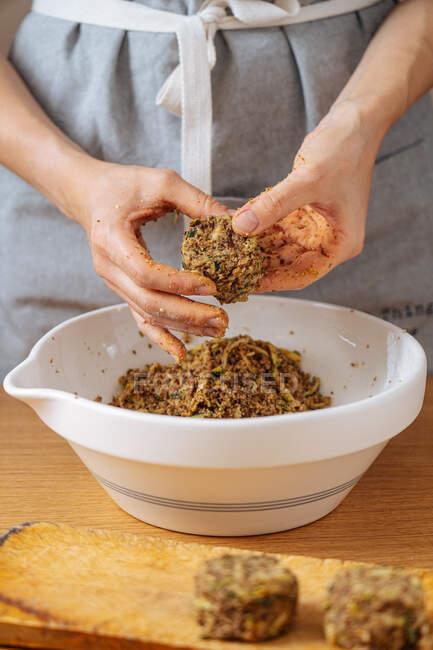 Erntehelferin macht leckere gesunde vegane Schnitzel aus Linsen und Zucchini am Holztisch mit weißer Schüssel — Stockfoto