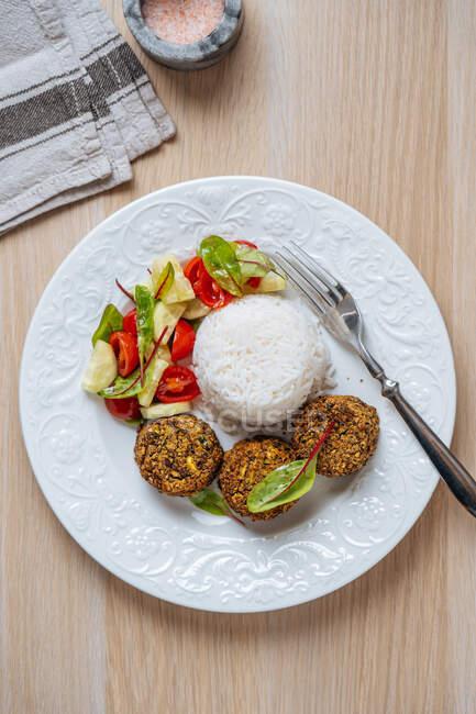 Vue en haut d'une assiette blanche avec des boutons végétaliens servis avec du riz blanc et une salade de légumes frais sur une table en bois — Photo de stock