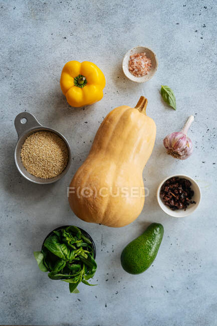 Top view of ingredients for preparing vegetarian dish with fresh yellow butternut pumpkin on stone background — Stock Photo