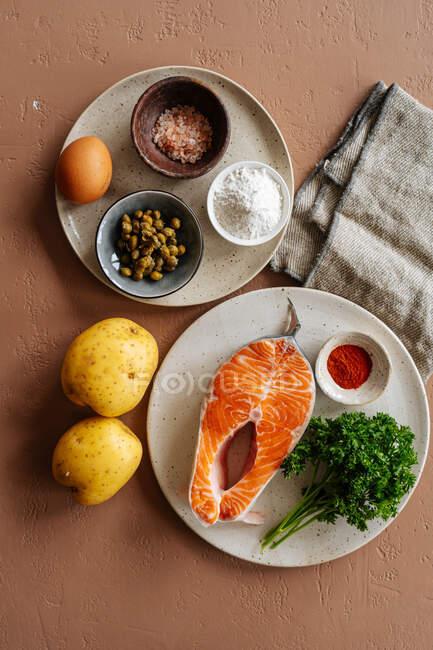 Зверху ви бачите інгредієнти до смачної страви з лососевим стейком і картоплею з травами і спеціями на коричневому тлі з тканиною. — стокове фото
