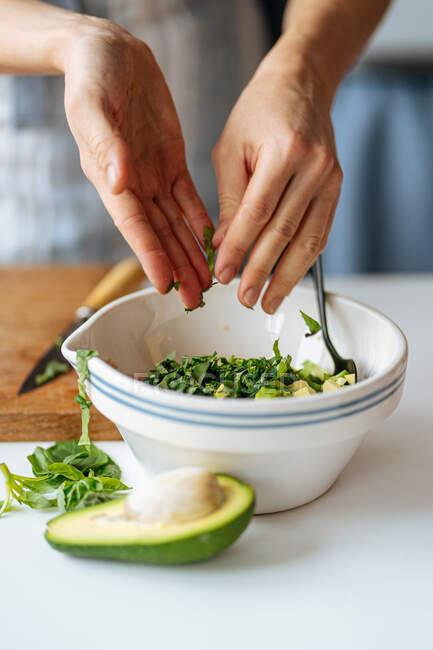 Mãos de colheita de dona de casa adicionando ervas verdes frescas picadas em tigela com abacate enquanto prepara comida na mesa branca na cozinha — Fotografia de Stock
