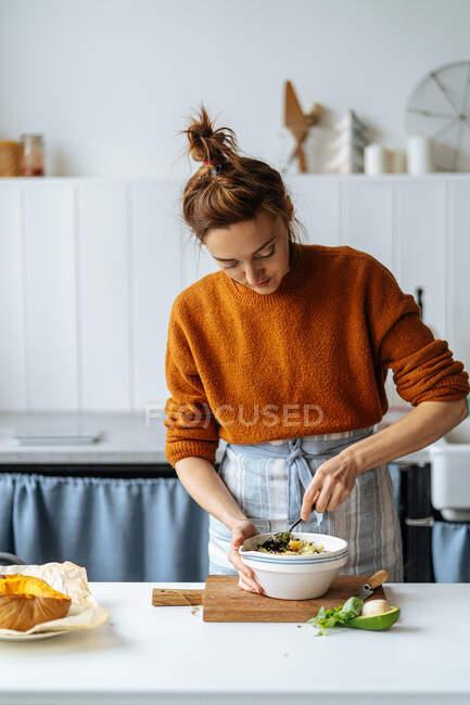Женщина добавляет изюм в миску — стоковое фото