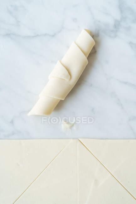 З - під сирого круїзана з нарізаним шматком тіста на мармуровому столі на кухні. — стокове фото