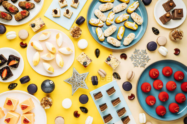 Top view of Christmas baubles and snowflakes placed near plates with various sweet pastry on yellow background — Stock Photo