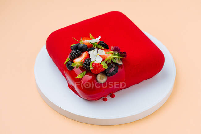 З понад квадратного торта з яскраво-червоним глазур'ям і різних свіжих ягід і квітів покладених на круглу дошку на персиковому фоні — стокове фото