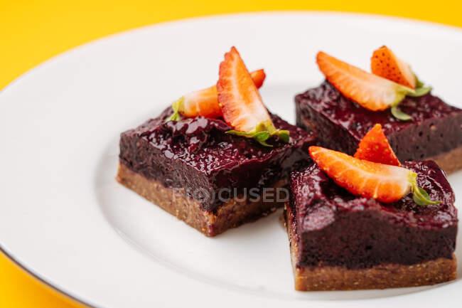 Одягніть шматочки смачного торта з шоколадом і полуницею на білу керамічну пластинку. — стокове фото
