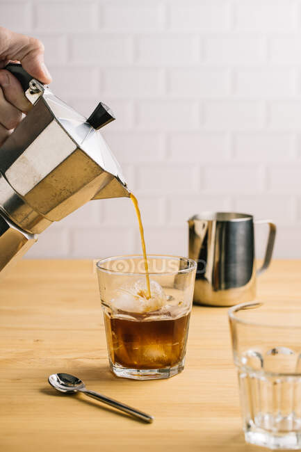 Crop person pouring coffee from coffeemaker into stylish glass with ice on wooden counter in cafe — Stock Photo