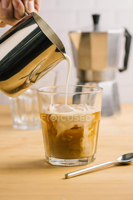 Unrecognizable barista filling glass of coffee with milk — Stock Photo