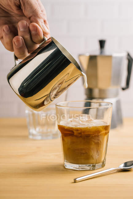 Professional faceless barista pouring milk from metal pitcher in glass with fresh ice coffee on wooden table in cafe — Stock Photo