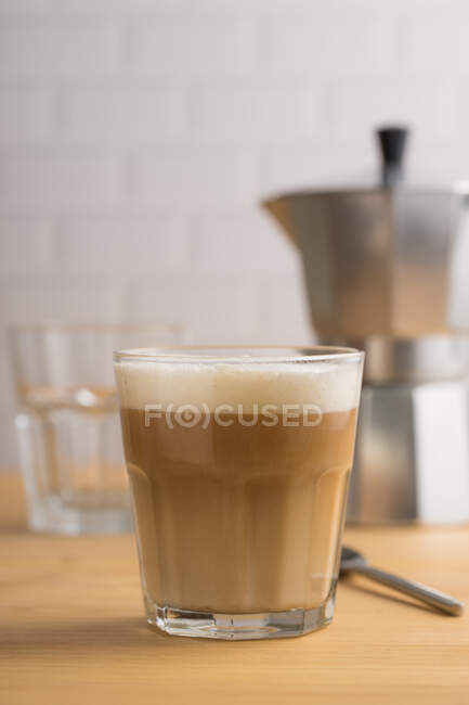 Transparent glass with tasty coffee with milk foam on wooden table with utensil on blurred background — Stock Photo