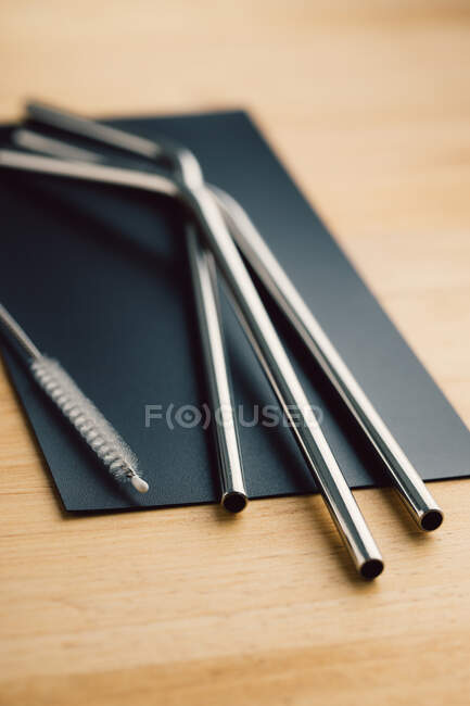 Top view of reusable metal straws and cleaning brush in row on wooden table — Stock Photo