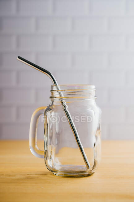Diverse cannucce di acciaio lucido in brocca di vetro vuota con manico su tavolo di legno — Foto stock