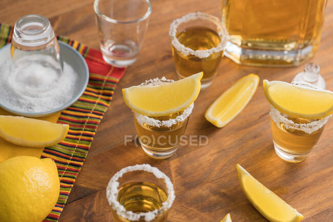 From above top view of glass shots of golden tequila with salty rim and slices of lemon on top on wooden table — Stock Photo