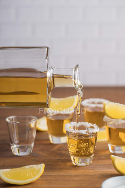 From above glass shots of golden tequila with salty rim and slices of lemon on top on wooden table — Stock Photo