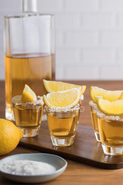 З - над скляних уламків золотої текіли з солоним ободом і шматочками лимона на дерев
