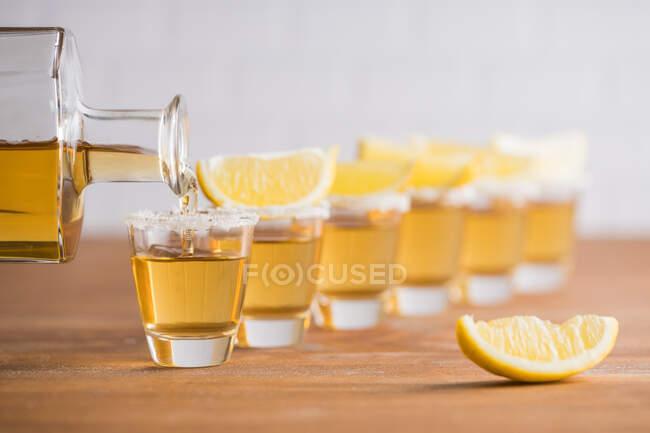 Ряд скляних чобіт із золотою текілою та шматочками лимона на дерев