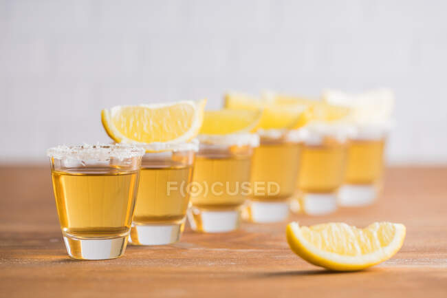 Row of glass sots with golden tequila and slices of lemon on wooden table with white wall on blurred background — Stock Photo