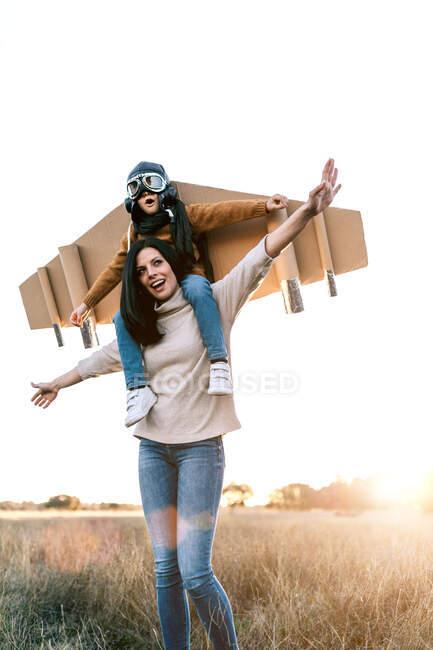 Joyeux garçon mignon portant des lunettes et des ailes en carton tout en étant assis sur les épaules de la mère et imitant aviateur sur la prairie dans le rétroéclairé — Photo de stock