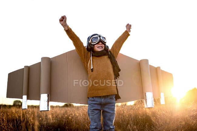 Criança feliz em óculos e asas de papelão levantando as mãos durante o jogo no campo em backlit — Fotografia de Stock