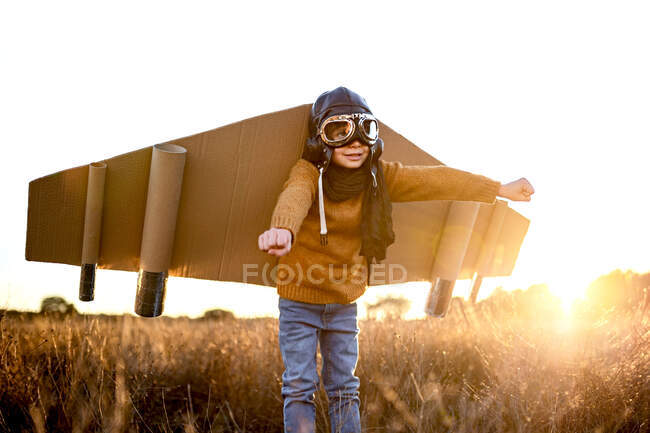 Happy kid in goggles and cardboard wings raising hands during game on field in backlit — Stock Photo
