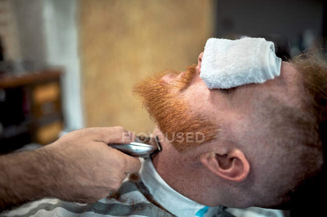 Ritagliato barbiere irriconoscibile con trimmer taglio rossa uomo barba con asciugamano che copre gli occhi seduto in barbiere — Foto stock