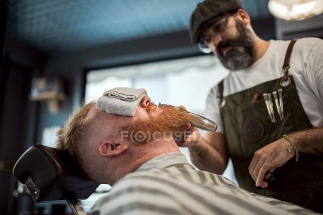Peluquero con peine y trimmer corte pelirrojo barba hombre con toalla que cubre los ojos sentado en la barbería - foto de stock
