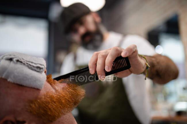 Barbiere sfocato irriconoscibile con pettine fissaggio rossa uomo barba con asciugamano che copre gli occhi seduto in barbiere — Foto stock