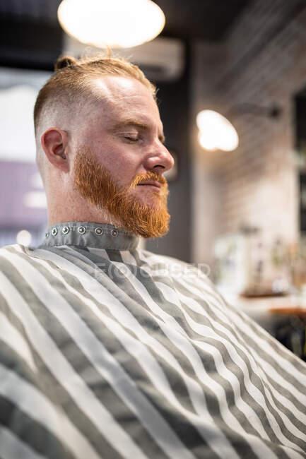 Рыжий сидит в современной парикмахерской с закрытыми глазами и ждет парикмахера. — стоковое фото