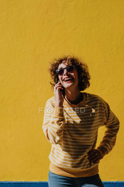 Casual joven turista hablando en el teléfono inteligente en la pared de colores — Stock Photo