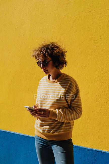 Незвичайна молода жінка дивиться смартфон біля яскравої стіни. — стокове фото