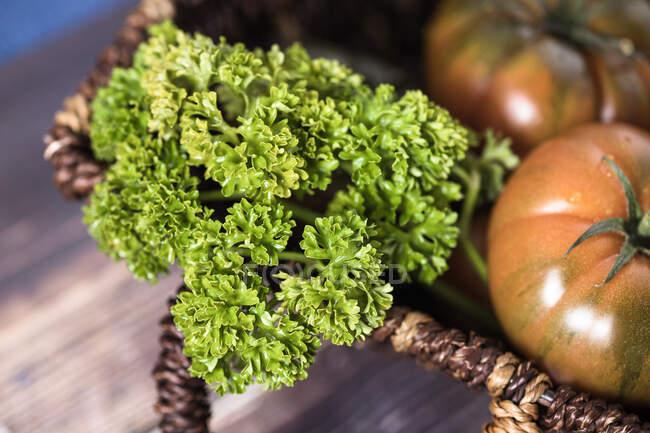 Одяг зверху свіжої зелені та червоних помідорів у кошику на столі. — стокове фото